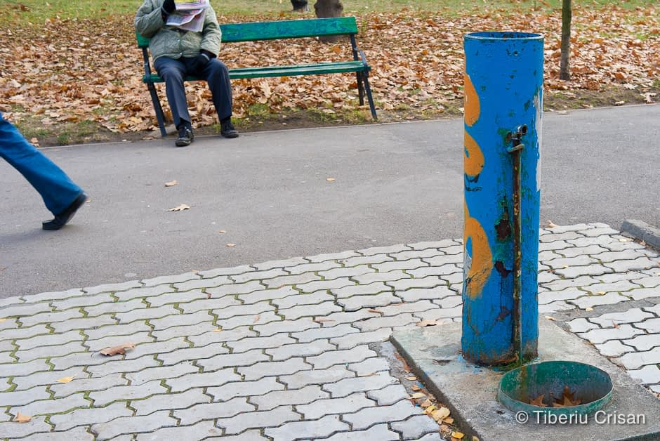 Imagine cu stalp albastru, om pe banca citind ziarul si picior oblic.