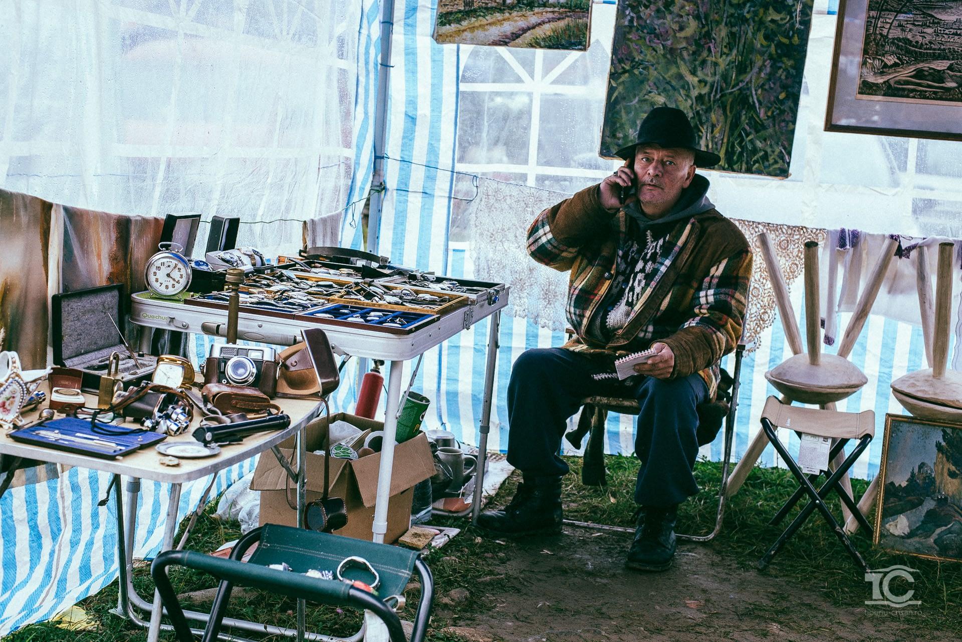 Un vanzator vorbeste la telefon la Targul de la Negreni