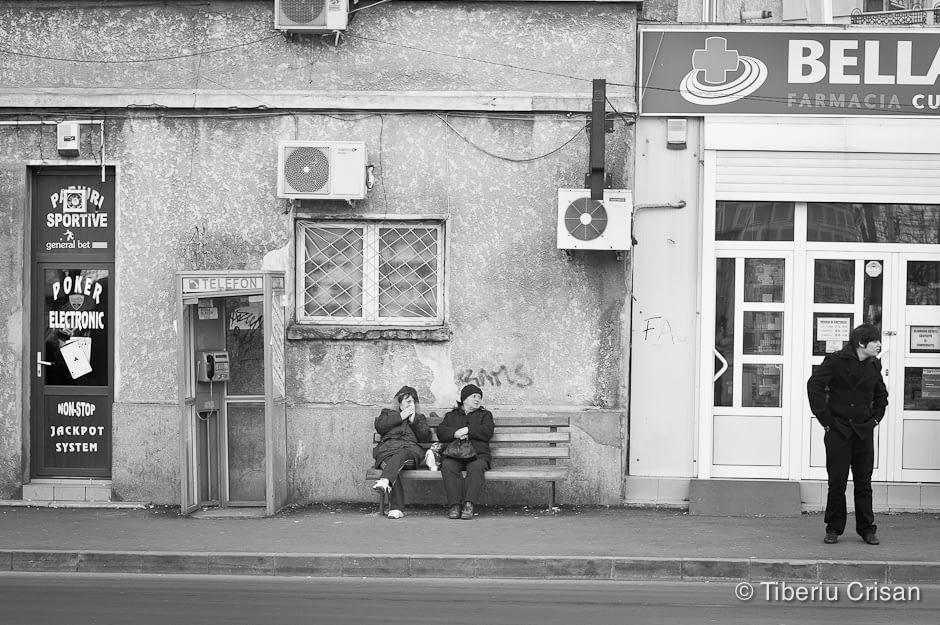 Doua doamne asteapta autobuzul pe banca